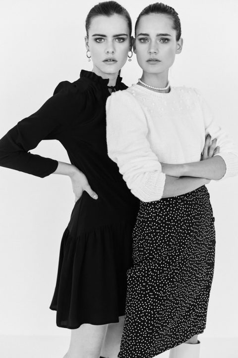 dwie modelki, jedna ubrana w czarną sukienkę mini, druga w sweterek oraz spódniczkę w grochy